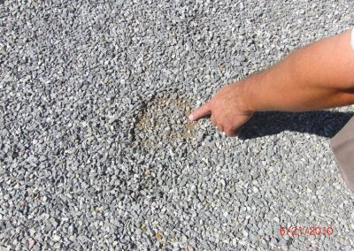 Expert Pointing Towards Gravel Damage Made By Hailstones