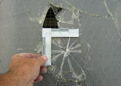 Inspector Measuring Damage To Broken Roof Glass Element